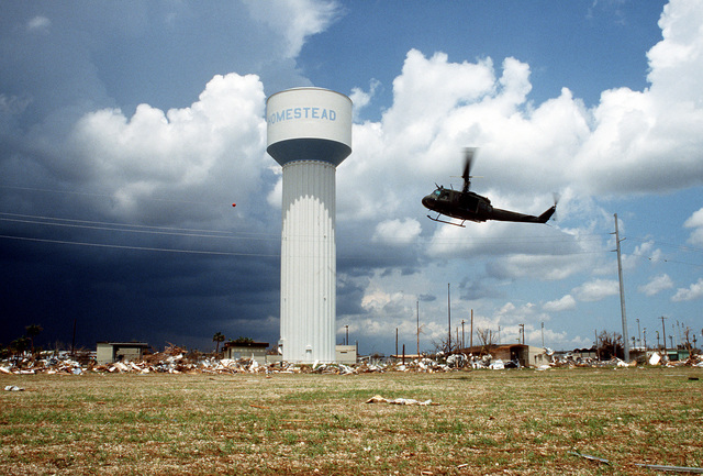 A UH-1 Iroquois helicopter hovers over the destruction caused by Hurricane Andrew while a water tower remains untouched by the storm. The hurricane struck the area on August 24th
