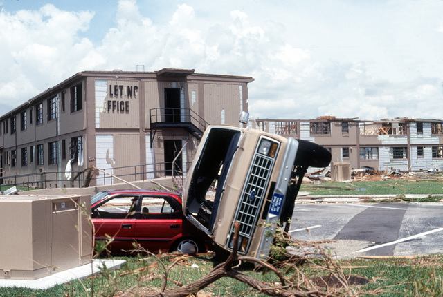 A van stands on its side atop another vehicle in the aftermath of Hurricane Andrew, which struck the area on August 24th