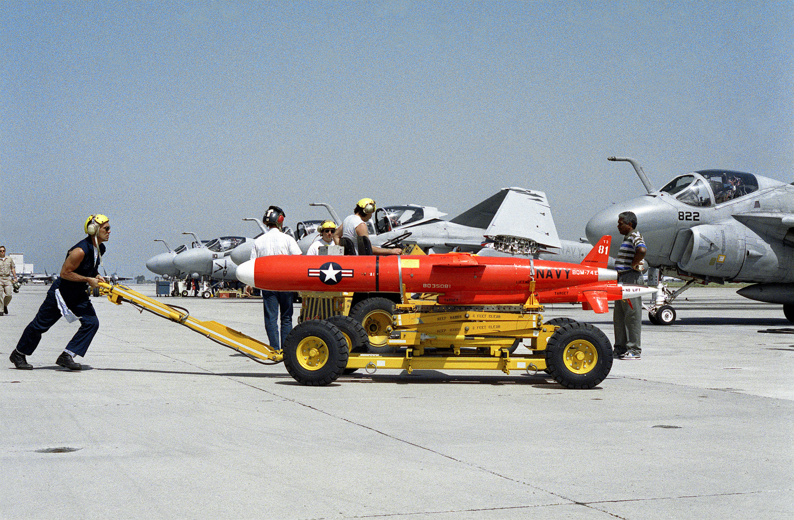 A weapons loader is used to move a BQM-74E target drone across the flight line during operational test and evaluation exercises conducted by the Missile Targets Division of the Naval Air Warfare Center Weapons Division. A-6E Intruder aircraft are in the background