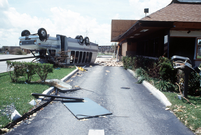 An overturned van lies on its roof in front of the operations center in the aftermath of Hurricane Andrew, which struck the area on August 24th