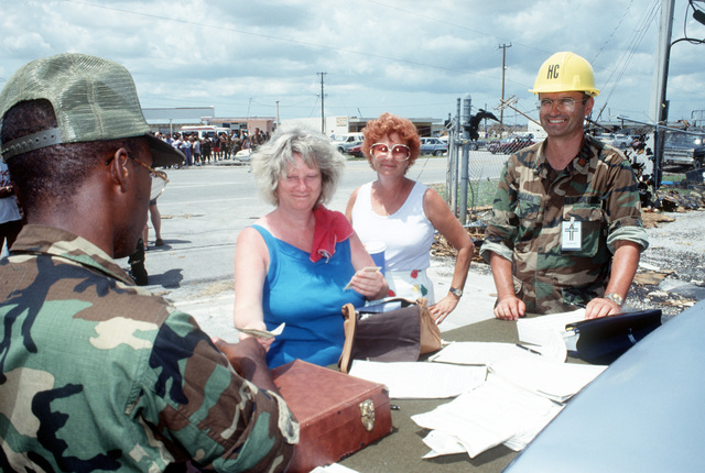 Base workers hand out relief funds to residents in the aftermath of Hurricane Andrew, which struck the area on August 24th