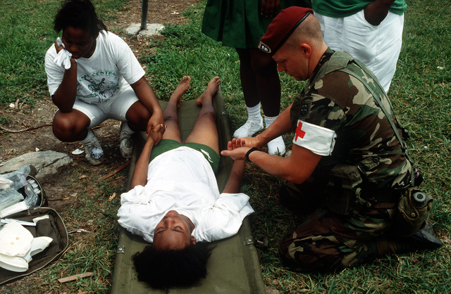 CAPT. Lewis, a medical officer of Co. B, 4th Bn., 325th Inf., 82nd Airborne Div., tends to a heat casualty during the Perrine parade. The event is being held in honor of the various military units in the area that assisted with cleanup efforts in the aftermath of Hurricane Andrew. The storm struck the region on August 24th