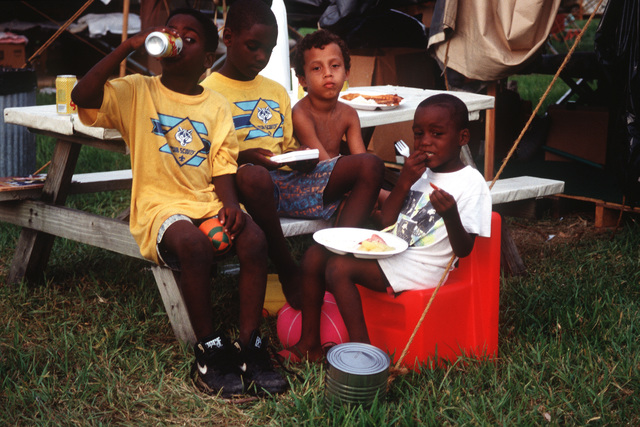 Children eat a meal at the U.S. Marine Corps Camp Two Life Support Center, a distribution point providing relief efforts and supplies to residents in the aftermath of Hurricane Andrew, which struck the region on August 24th