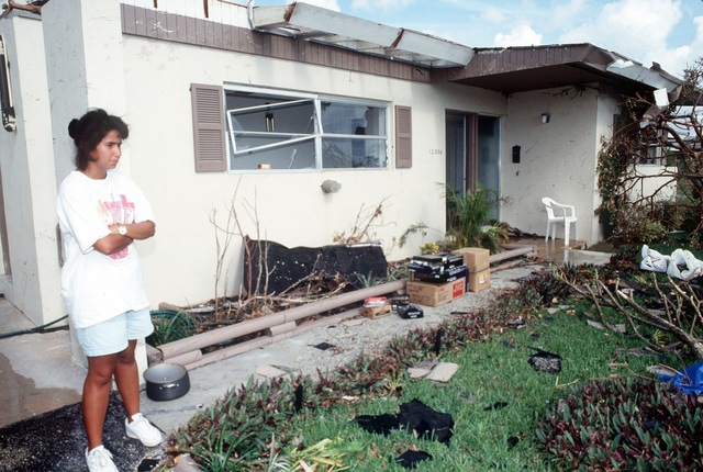 Debbie Gurnari, wife of TECH. SGT. Buddy Gurnari, surveys her damaged on-base quarters in the aftermath of Hurricane Andrew, which struck the area on August 24th