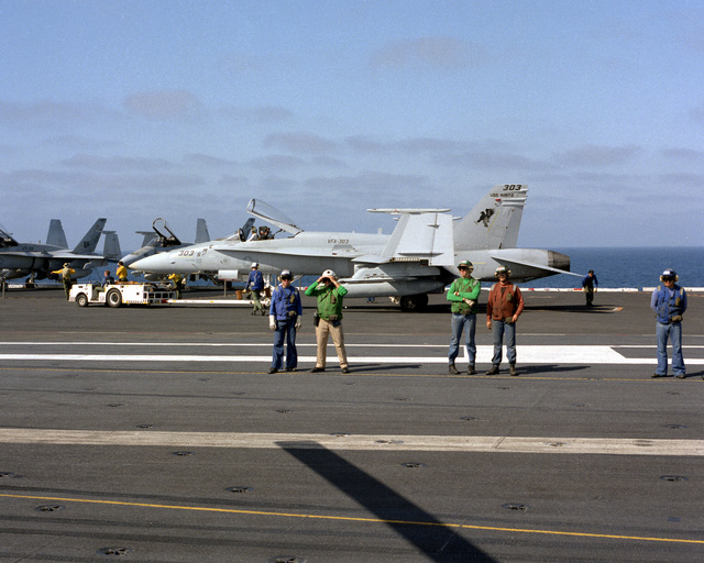 Flight deck personnel stand by as a Fighter Attack Squadron 303 (VFA-303) F/A-18A Hornet aircraft is serviced aboard the nuclear-powered aircraft carrier USS NIMITZ (CVN-68). The Reserve Carrier Air Wing 30 (CVWR-30) squadron is embarked aboard the NIMITZ for a two-week annual training period