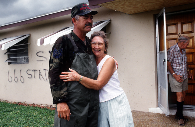 MASTER SGT. Roger L. Horton, 202nd Red Horse Civil Engineering Squadron, receives a hug from a local resident grateful for his assistance in cleaning up in the aftermath of Hurricane Andrew, which struck the area on August 24th
