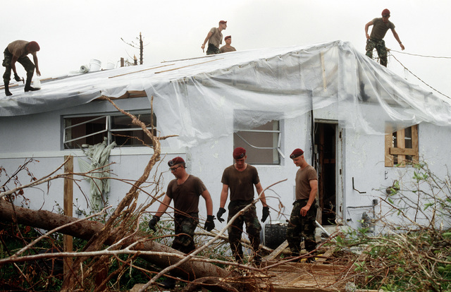 Members of the 202nd Red Horse Civil Engineering Squadron repair the roof on a foster child care facility in the aftermath of Hurricane Andrew, which struck the area on August 24th