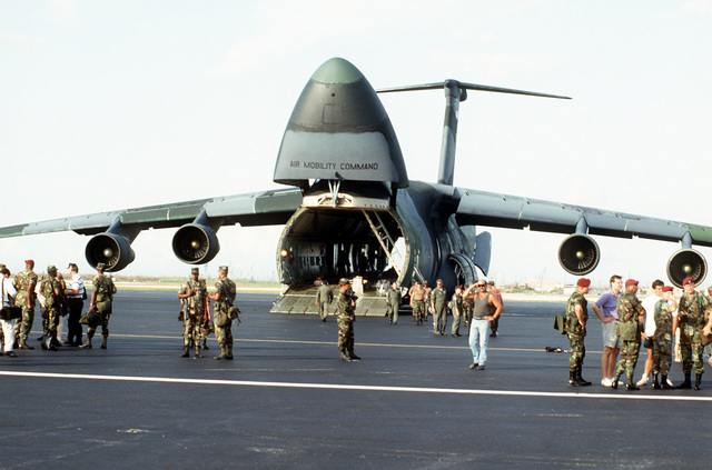 Military personnel disperse after unloading supplies from a C-5A Galaxy aircraft in the aftermath of Hurricane Andrew, which struck the area on August 24th
