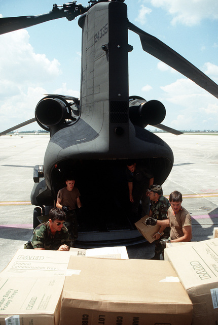 National Guardsmen load relief supplies into a CH-47 Chinook helicopter at Opa-Locka Coast Guard Air Station for distribution to Homestead Air Force Base and surrounding areas damaged during Hurricane Andrew. The storm struck the area on August 24th