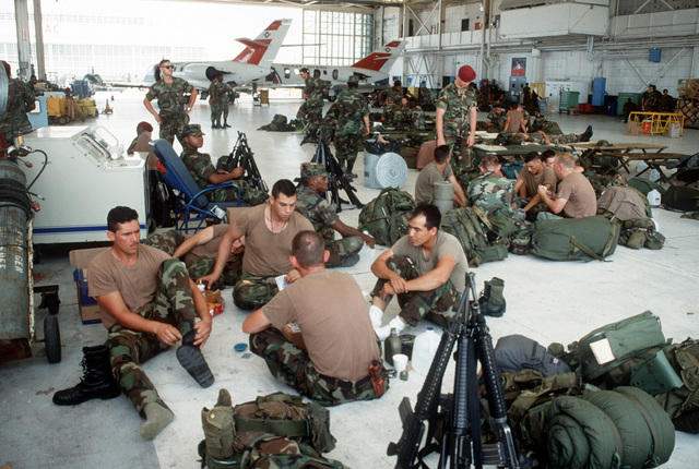 Personnel from the 55th Medical Group, 44th medical Brigade, relax in a hangar at Opa-Locka Coast Guard Air Station before moving out to assist with relief efforts for area residents in the aftermath of Hurricane Andrew. The storm struck the region on August 24th