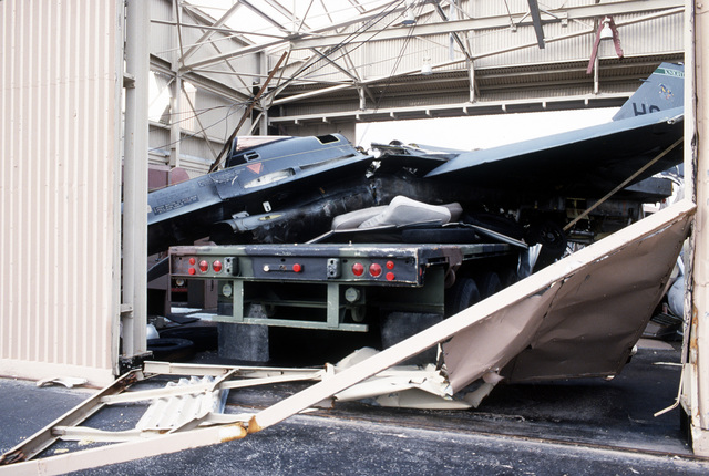 Pieces of a demolished F-16C Fighting Falcon aircraft lie on top of a truck in a destroyed hangar. The damage was caused by Hurricane Andrew, which struck the area on August 24th