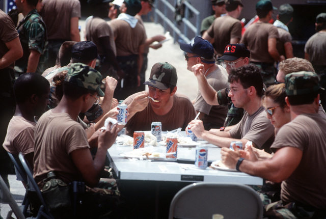 Relief workers and base personnel eat lunch in the base exchange parking lot during Hurricane Andrew cleanup efforts. The storm struck the area on August 24th