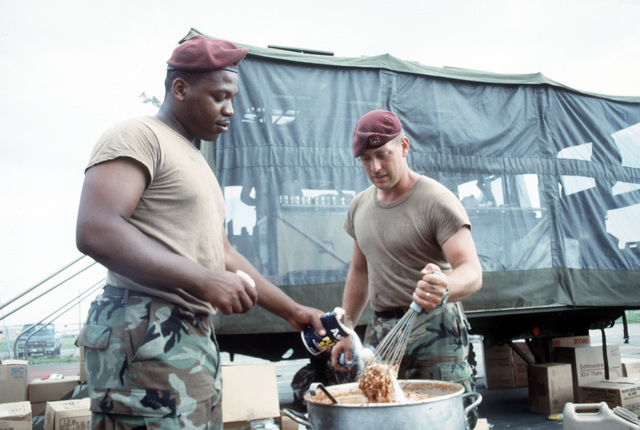 SGT. Jerome Crouthmel, left, and SGT. Russel King of C Btry., 1ST Bn., 116th Field Arty., Air National Guard, prepare food for area residents left homeless by Hurricane Andrew, which struck the area on August 24th