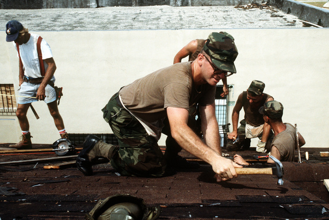 SGT. Scott Anderson, Company A, 10th Mountain Division (Light Infantry), hammers shingles on a roof as he repairs damage caused by Hurricane Andrew, which struck the region on August 24th