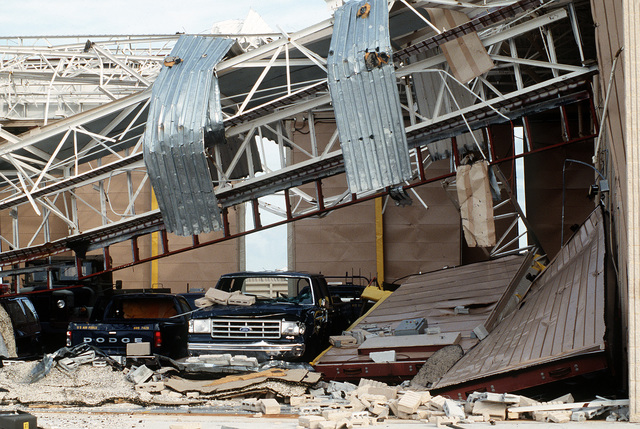 Trucks stand in a demolished hangar which sustained the damage during Hurricane Andrew. The storm struck the area on August 24th