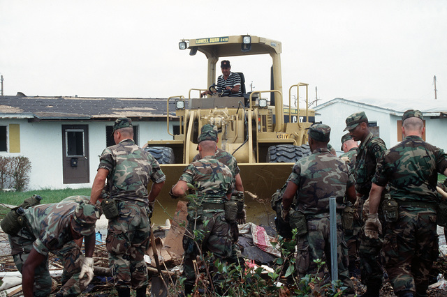 U.S. Army personnel assist civilian workers in cleaning up debris in the aftermath of Hurricane Andrew, which struck the area on August 24th
