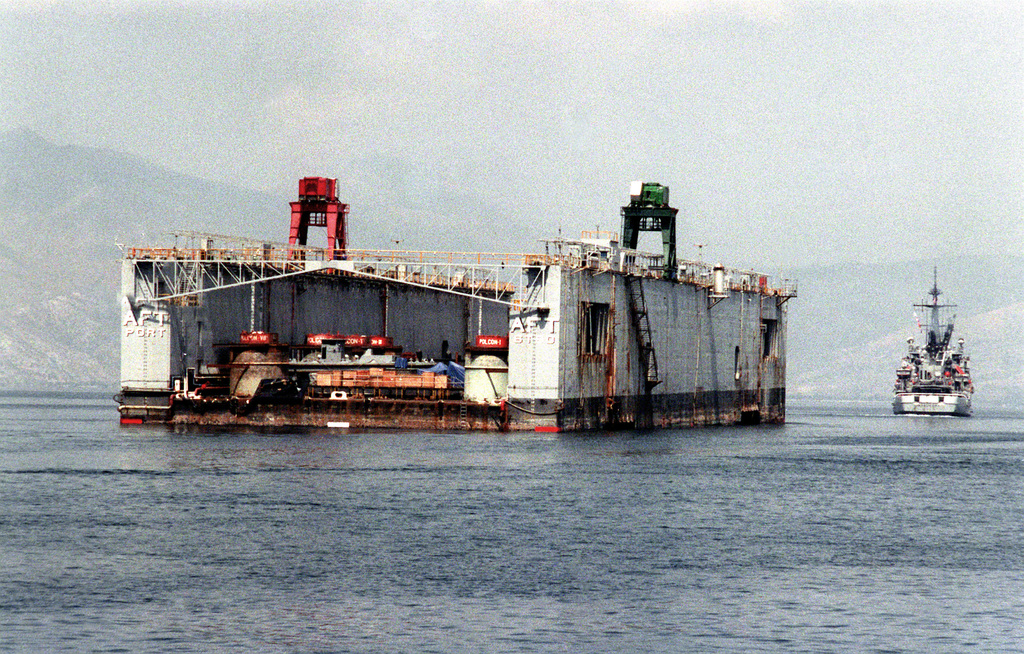 A dry dock is towed from Naval Station, Subic Bay, by the salvage and rescue ship USS BEAUFORT (ATS-2) as ordnance and equipment is removed in preparation for the station's closure. Subic Bay Metropolitan Authority will assume control of the area after the U.S. Navy relinquishes the station