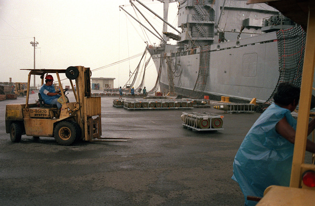 A forklift is positioned near a crate of ordnance prior to loading it aboard the cargo ship BUYER (T-AK-2033). Equipment and ordnance is being removed from the area as the U.S. Navy prepares to close the station and relinquish it to the Subic Bay Metropolitan Authority