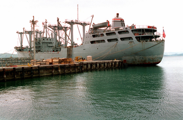 A port quarter view of the cargo ship Buyer (T-AK-2033) docked at a pier as it takes on containers of ordnance in preparation for the closing of the naval station. Following closure, the Subic Bay Metropolitan Authority will assume control of the area