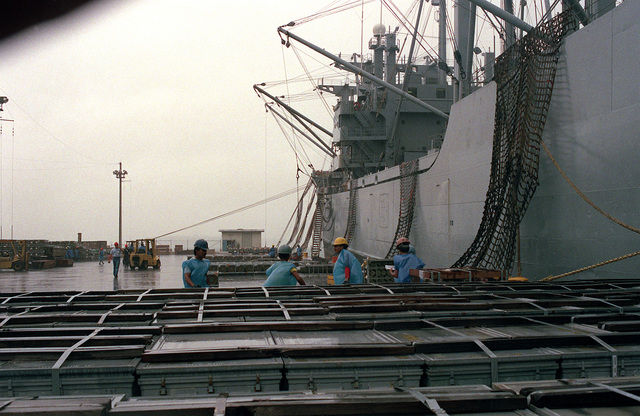 Crates of ammunition line the pier in preparation for loading aboard the cargo ship BUYER (T-AK-2033), moored at right. Ordnance and equipment are being removed from the area as the U.S. Navy prepares to close the station and relinquish it to the Subic Bay Metropolitan Authority