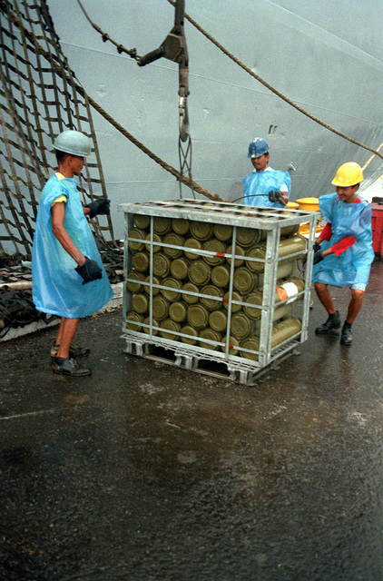 Dock workers prepare to load crates of ordnance on the cargo ship BUYER (T-AK-3033) as ordnance and equipment is removed from the area prior to the closing of the station. The U.S. Navy is relinquishing control of NAS, Cubi Point, to the Subic Bay Metropolitan Authority