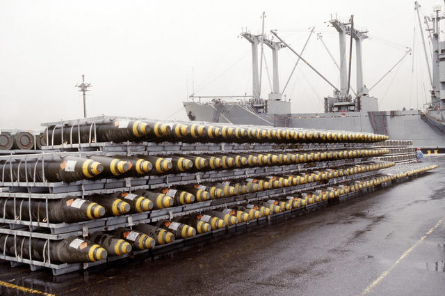 Ordnance racks holding bombs line a pier beside the cargo ship BUYER (T-AK-2033) prior to being loaded aboard the vessel. Ordnance and equipment is being removed from the area as the U.S. Navy prepares to close the station and relinquish it to the Subic Bay Metropolitan Authority