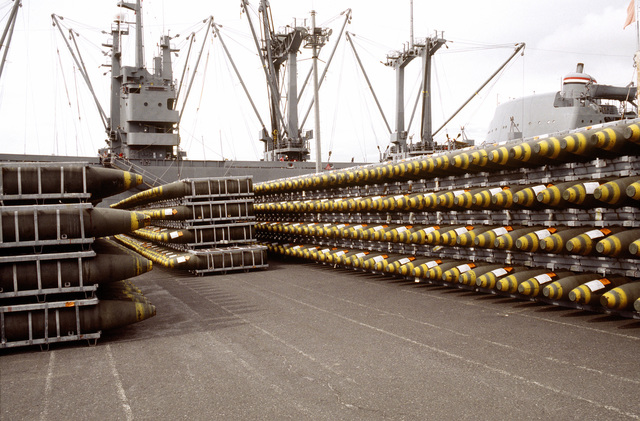 Ordnance racks holding bombs line a pier prior to being loaded aboard the cargo ship BUYER (T-AK-2033). Ordnance and equipment is being removed from the area as the U.S. Navy prepares to close the station and relinquish it to the Subic Bay Metropolitan Authority