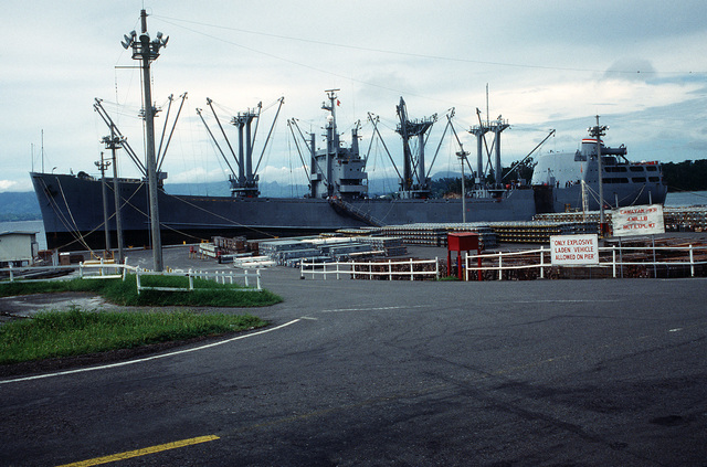 Racks of ordnance line the pier beside the cargo ship BUYER (T-AK-2033) prior to being loaded aboard the vessel. Ordnance and equipment is being removed from the area as the U.S. Navy prepares to close the station and relinquish it to the Subic Bay Metropolitan Authority