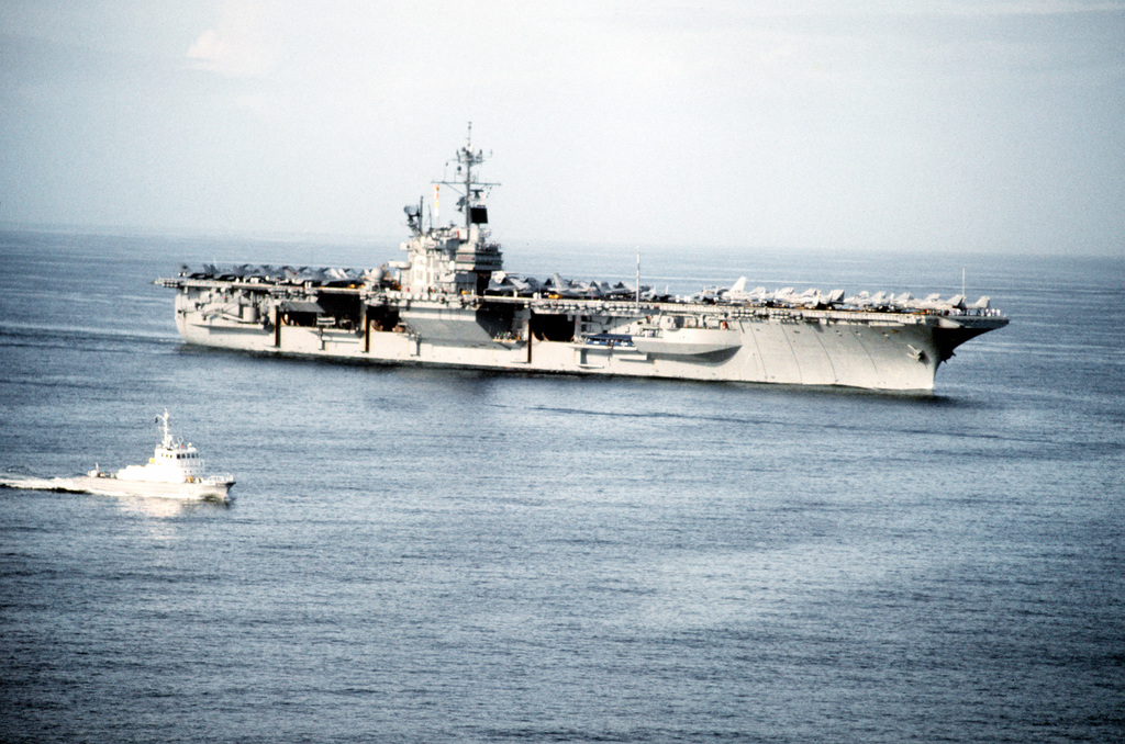 A Japanese Akizuki class patrol craft escorts the aircraft carrier USS RANGER (CV-61) toward port at Yokosuka as the vessel visits Japan for the last time. The RANGER is on its final deployment prior to decommissioning