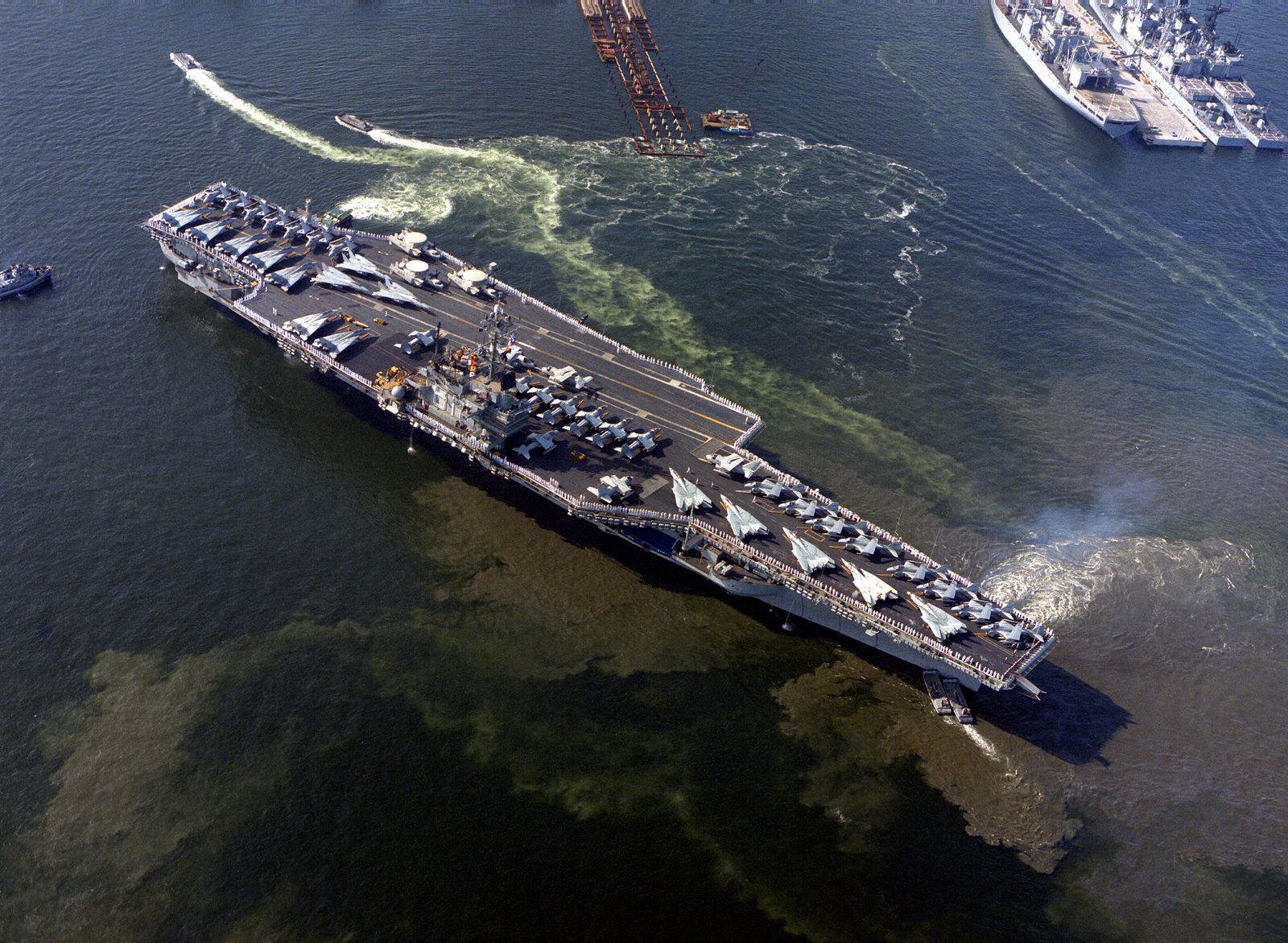 Large harbor tugs maneuver the aircraft carrier USS RANGER