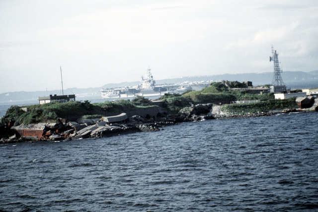 The aircraft carrier USS RANGER (CV-61) passes the remnants of a coastal fort on an island now used as a communications monitoring point. The RANGER is visiting Japan for the last time while on its final deployment prior to decommissioning