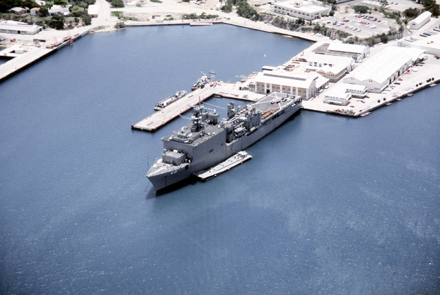 An overhead, starboard view of the dock landing ship USS ASHLAND (LSD-48) Med-moored in port. The ASHLAND is taking on supplies destined for Flordia communities devastated by Hurricane Andrew as part of Operation Help From the Sea