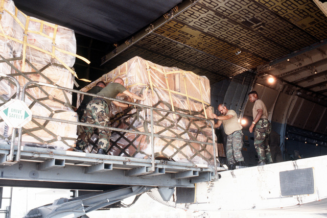 Military personnel load palletized supplies on an Air Force C-5 Galaxy aircraft. The supplies will be delivered to Flordia communities devastated by Hurricane Andrew as part of Operation Help From the Sea