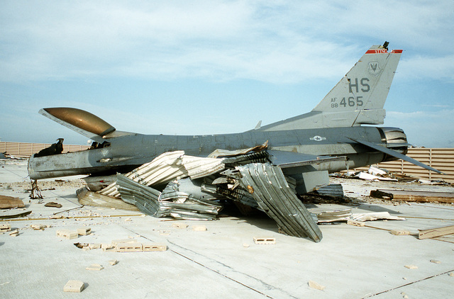 A destroyed F-16C Fighting Falcon aircraft lies on the tarmac in the aftermath of Hurricane Andrew, which struck the area on August 24th