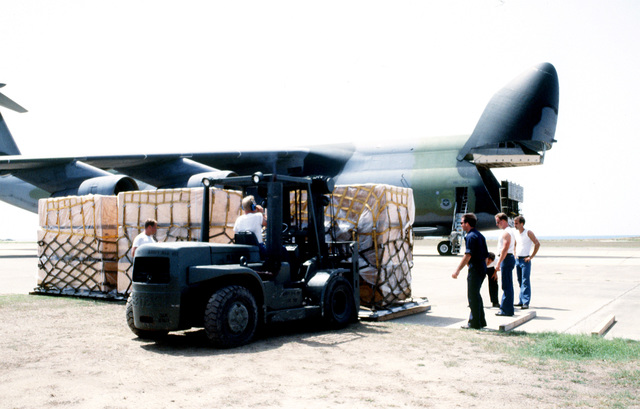 A forklift is used to pick up a pallet of supplies to be loaded on the Air Force C-5 GAlaxy aircraft in the background. The supplies will be delivered to Florida communities devastated by Hurricane Andrew as part of OPERATION HELP FROM THE SEA