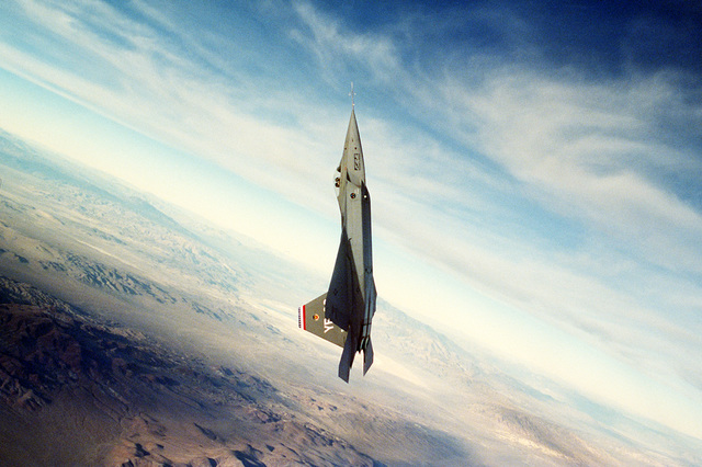 "An air-to-air right side view of an YF-22 advanced tactical fighter aircraft during a test flight. The aircraft represents the latest developments in stealth or ""low observable"" technology."