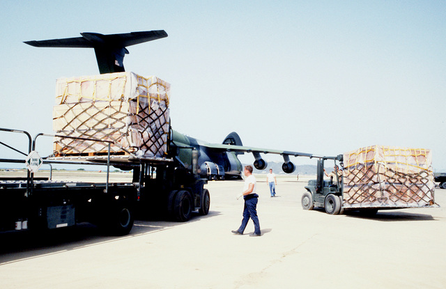 Forklifts are used to lad palletized supplies on a K-loader that will then load the supplies on the Air Force C-5 Galaxy aircraft in the background. The supplies are destined for Florida communities devastated by Hurricane Andrew as part of OPERATION HELP FROM THE SEA