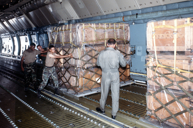 Military personnel position palletized supplies on an Air Force C-5 Galaxy aircraft. The supplies will be delivered to Flordia communities devastated by Hurricane Andrew as part of Operation Help From the Sea