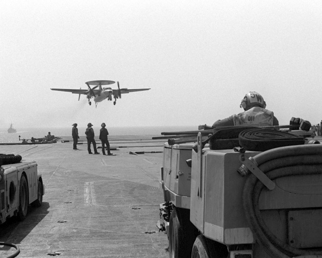 An E-2C Hawkeye aircraft approaches the flight deck of the aircraft carrier USS INDEPENDENCE (CV-62). The INDEPENDENCE is participating in Operation Southern Watch, a multinational effort establishing a no-fly zone for Iraqi aircraft south of the 32nd parallel in Iraq. A flight deck cleaning vehicle is in the foreground