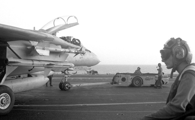 Flight deck crewmen use an MD-3 tow tractor to move an F-14 Tomcat aircraft on the aircraft carrier USS INDEPENDENCE (CV-62). The INDEPENDENCE is participating in Operation Southern Watch, a multinational effort establishing a no-fly zone for Iraqi aircraft south of the 32nd parallel in Iraq. The Tomcat has an AIM-9 Sidewinder missile mounted on the outboard wing pylon and an AIM-7 Sparrow missile mounted on the inboard pylon