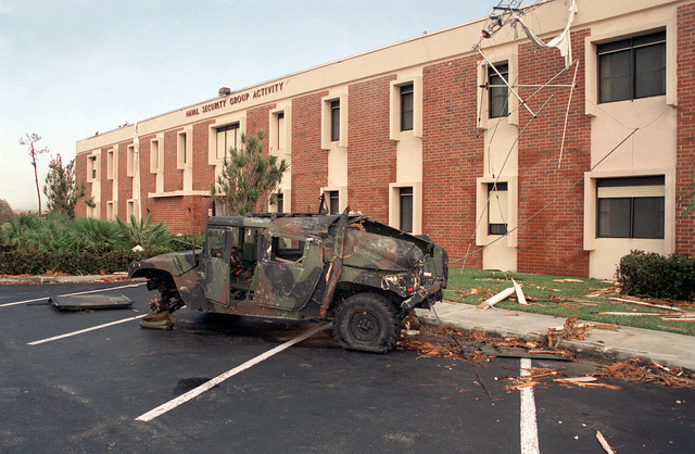 A damaged M998 High-Mobility Multipurpose Wheeled Vehicle (HMMWV), one of numerous vehicles destroyed by Hurricane Andrew, stands in front of the Naval Security Group Activity building