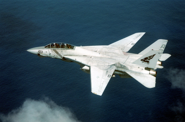 A overhead left side view of an F-14B Tomcat aircraft of Fighter Squadron 143 (VF-143) in flight near Puerto Rico. The aircraft has its wings swept forward for sub-sonic flight such as landing and take-offs and holding in the flight pattern