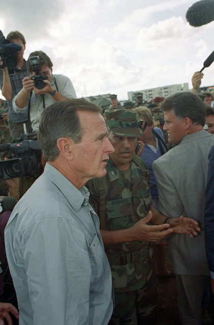 An Army officer speaks with President George Bush as the chief executive tours the area to assess damage in the aftermath of Hurricane Andrew