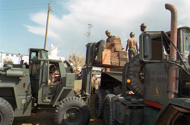 Members of a naval mobile construction battalion (Seabees) position construction material onto a forklift during disaster relief efforts in the aftermath of Hurricane Andrew