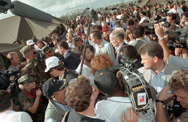 Members of the media gather around President George Bush as he meets with military personnel and civilians during his tour of the region. Bush is in Florida to assess damage and observe disaster relief efforts in the aftermath of Hurricane Andrew