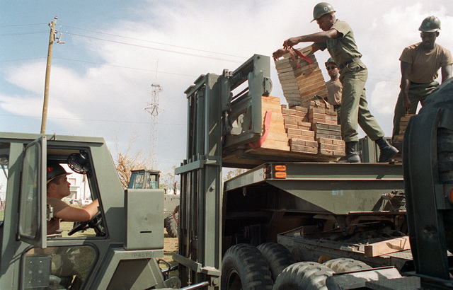 Military personnel position construction materials onto a forklift during disaster relief efforts in the aftermath of Hurricane Andrew
