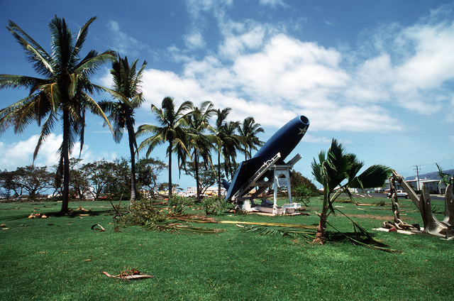 Palm fronds litter the ground around a RGM-6/15 Regulus surface-to-surface missile display damaged by Hurricane Iniki