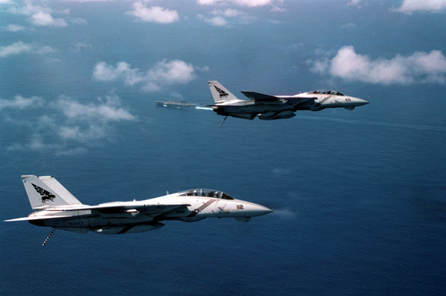 Right side view of two F14B Tomcat aircraft of Fighter Squadron 143 (VF-143) with tail hooks down in preparation for landing on board the USS GEORGE WASHINGTON (CVN-73) near Puerto Rico