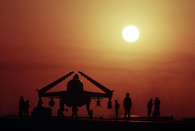 Silhouetted by the setting sun, flight deck crewmen work to secure an EA-6B Prowler aircraft on the flight deck of the aircraft carrier USS INDEPENDENCE (CV-62). The INDEPENDENCE is participating in OPERATION SOUTHERN WATCH, a multinational effort establishing a no-fly zone for Iraqi aircraft south of the 32nd parallel in Iraq