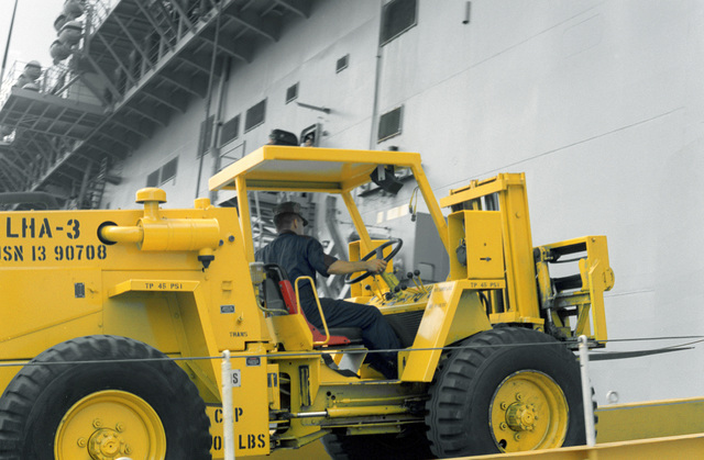 An M4K forklift is driven aboard the amphibious assault ship USS BELLEAU WOOD (LHA-3) as equipment of the 25th Infantry Division is readied for transport to the island of Kauai during Task Force Garden Isle, a joint military disaster relief effort being conducted in the aftermath of Hurricane Iniki